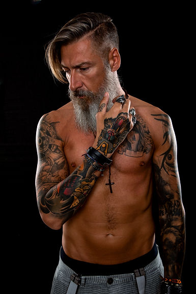 Portrait of a shirtless bearded, tattooe