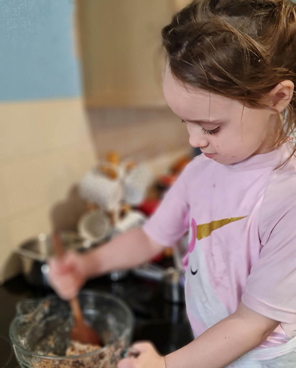 Little girl standing at the cooker stirring a mixing bowl of ingredients