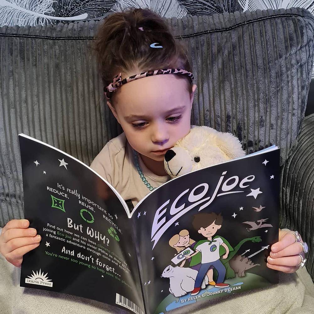 Young girl cuddling a polar bear toy and reading the Eco Joe book