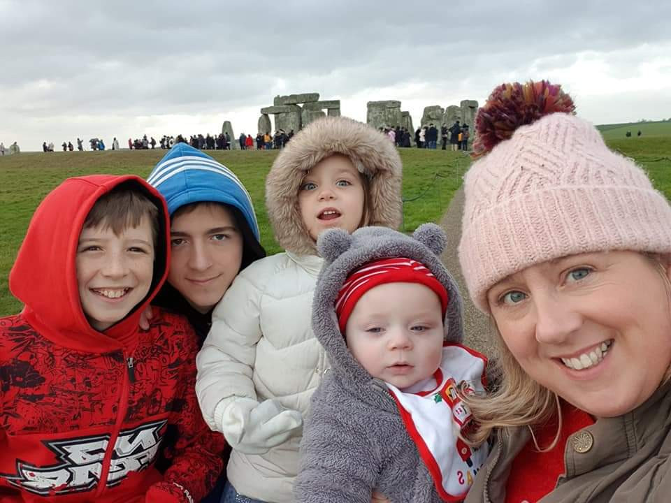 Sophie with her 4 children posing in front of Stonehenge