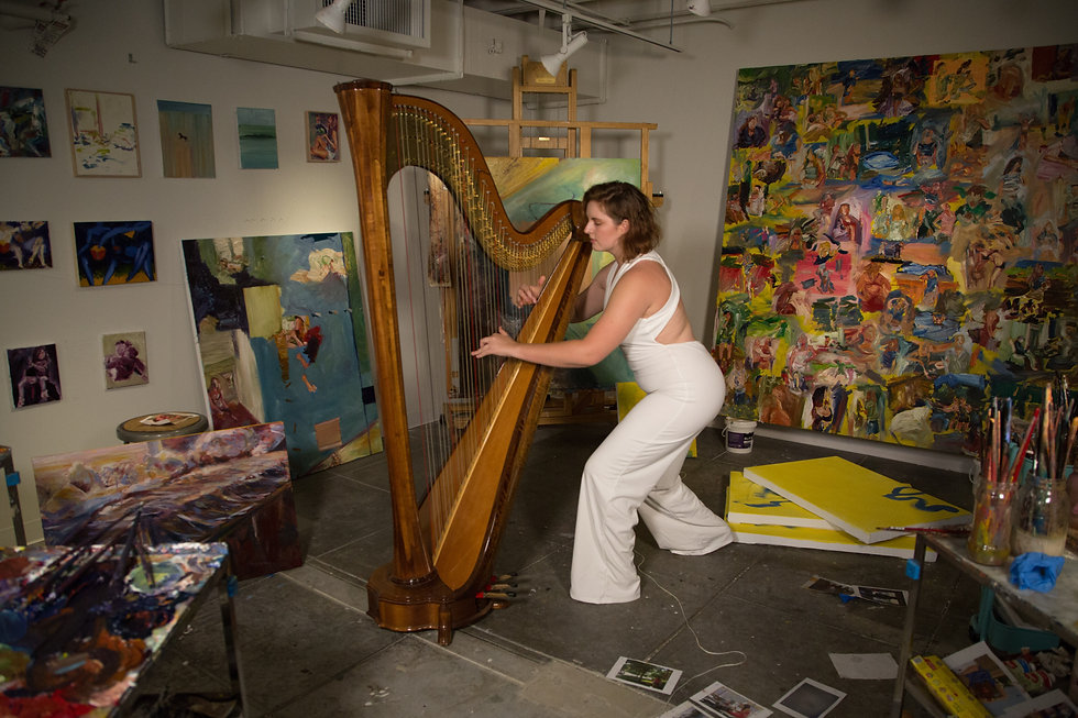 Artist Tori Parrish playing her harp in her studio, surrounded by paintings