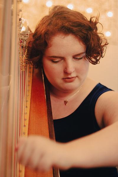 Close up image of Asheville Harpist Tori Parrish playing harp