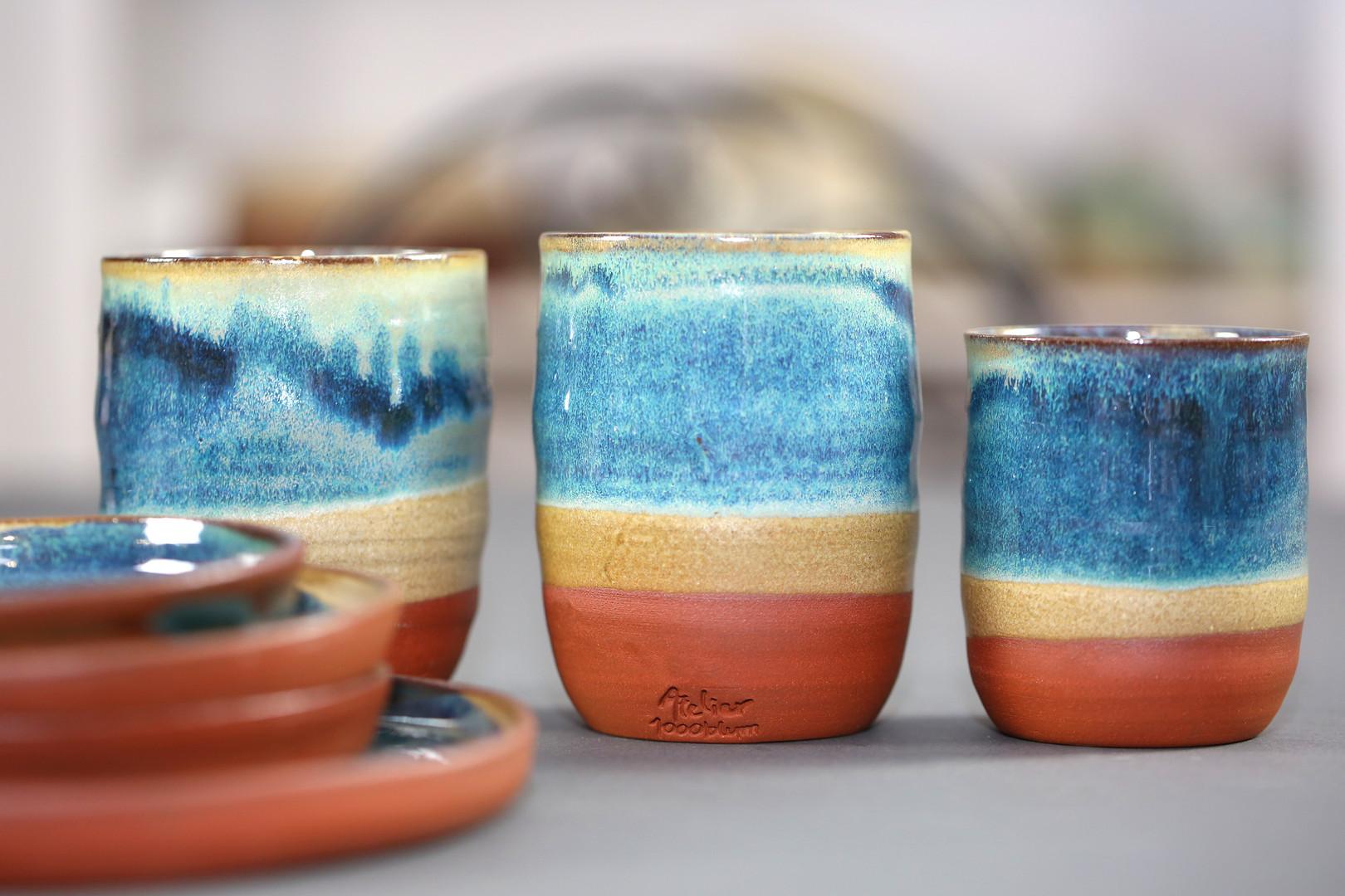 Becher und Teller mit meerblauer Glasur
