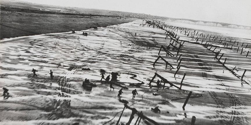 RAF aircraft buzzes Normandy beach obstacles