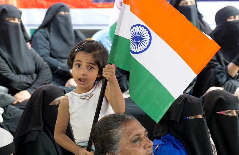 A little girl at the Tannery Road protest wields an Indian flag.