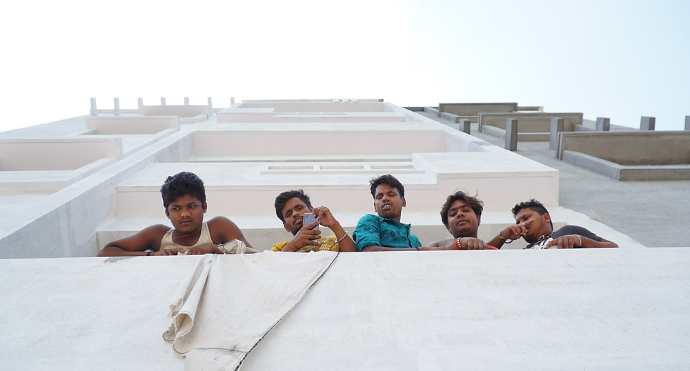 A group of migrant construction workers from the state of Bihar wair at their construction site for food to appear.