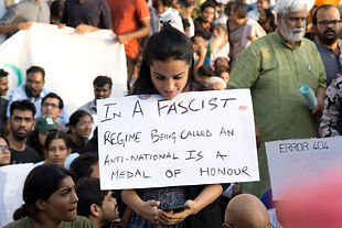 An art student holds a placard condemning the Modi administration.