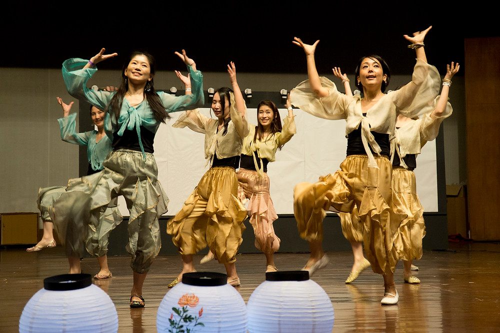 A group ofjapanese expat women and businesswomen do a Bollywood dance.
