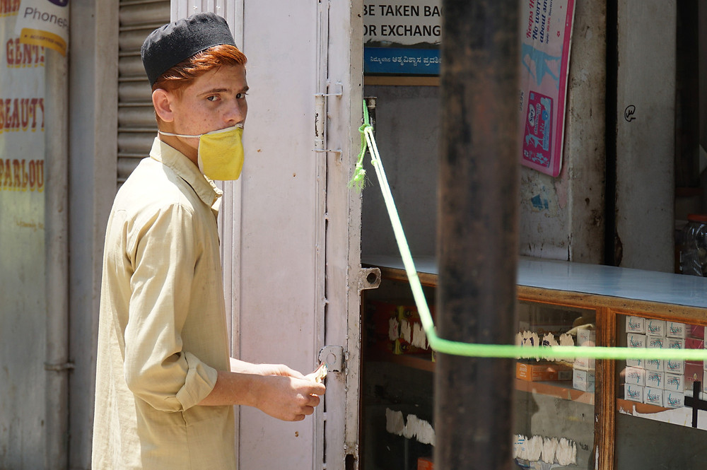 A boy waits to buy medicine within a Covid quarantine zone.