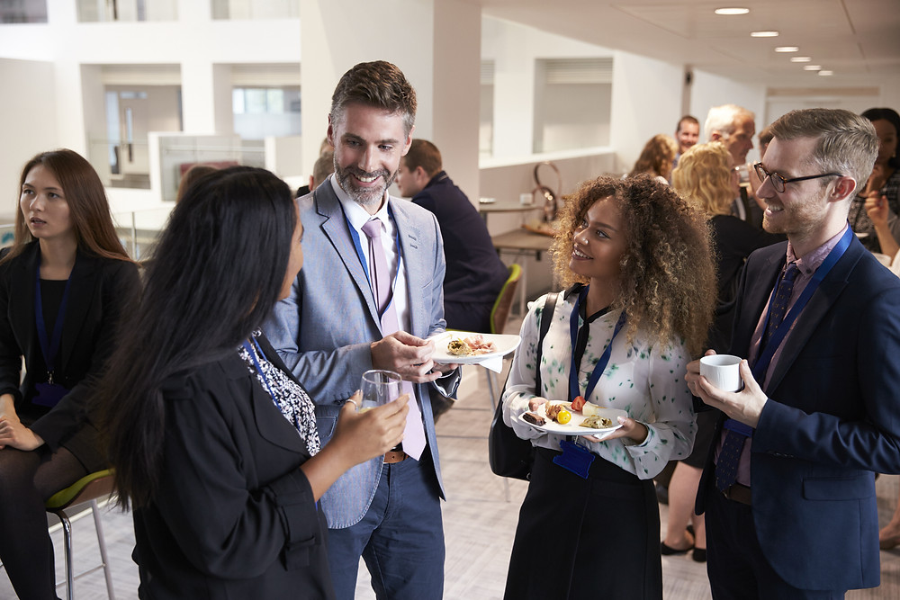 hroup of people talking  in a networking event