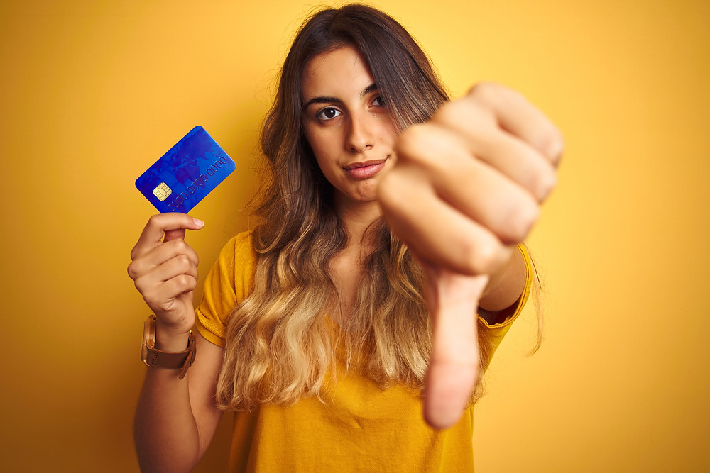 lady holding a credit card and other hand shwoing thumbs down
