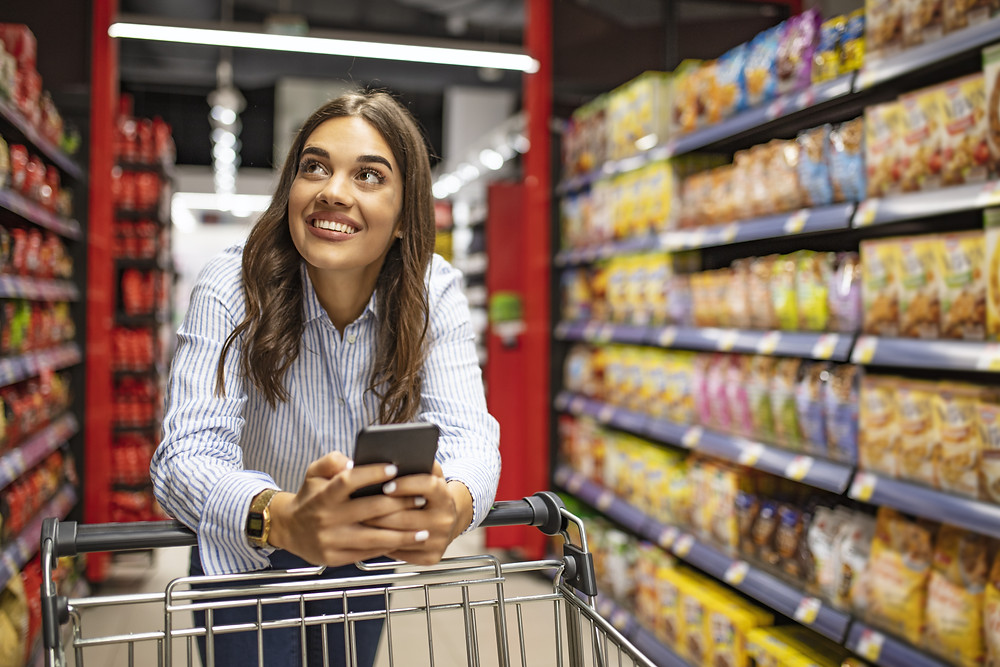 Boss of My Money Food Budget - lady holding phone smiling in supermarket