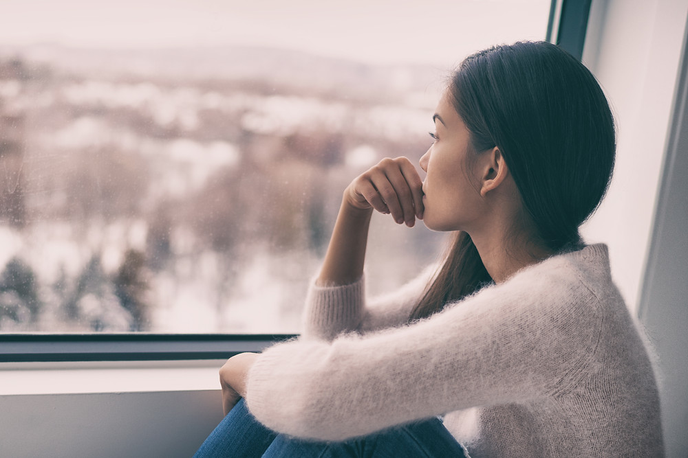 Lady looking worried looking outisde a window