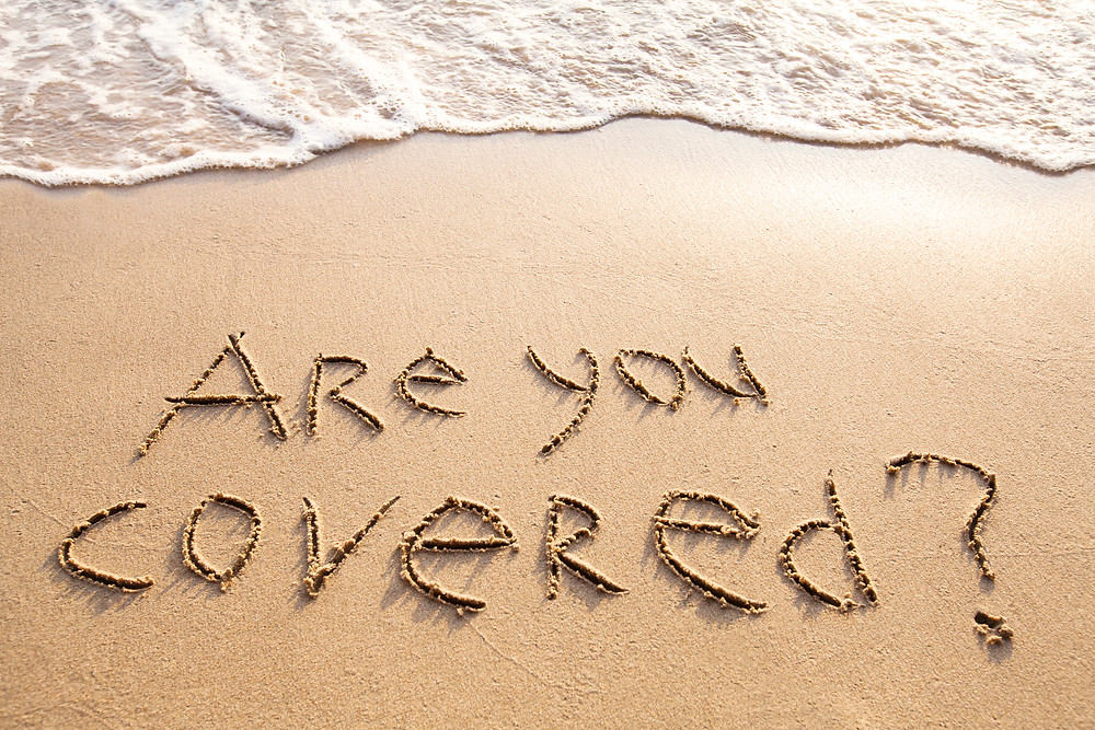 sandy beach with text are you covered drawn in sand