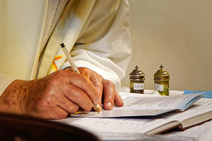 1200-511319836-priest-writing-on-book.jp