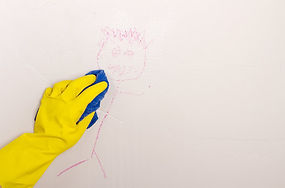 Cleaning off crayon on the wall with towel and gloves on
