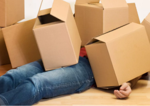 Person under pile of moving boxes