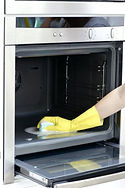 Woman professionally cleaning a dirty oven