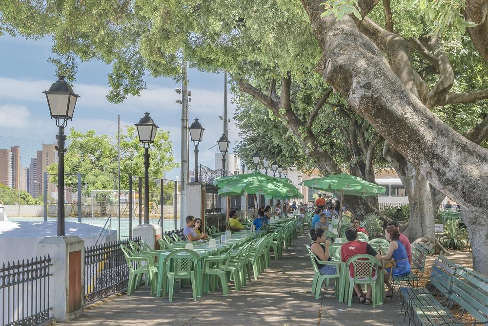Clientes de um restaurante descansando em mesas colocadas na calçada da Praça dos Mártires, a mais antiga de Fortaleza
