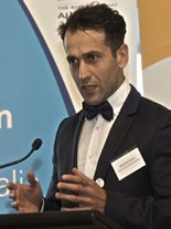 Photo of Associate Professor Mo Dirani standing at a podium, in front of a Vision 2020 Australia banner.