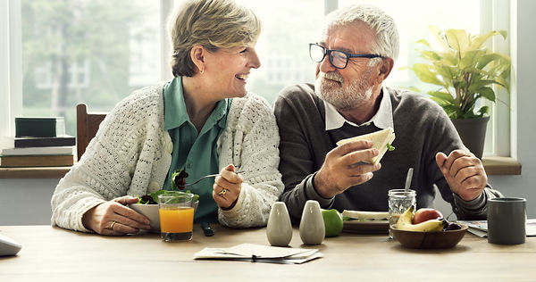 An elderly man and woman enjoying a healthy breakfast at home