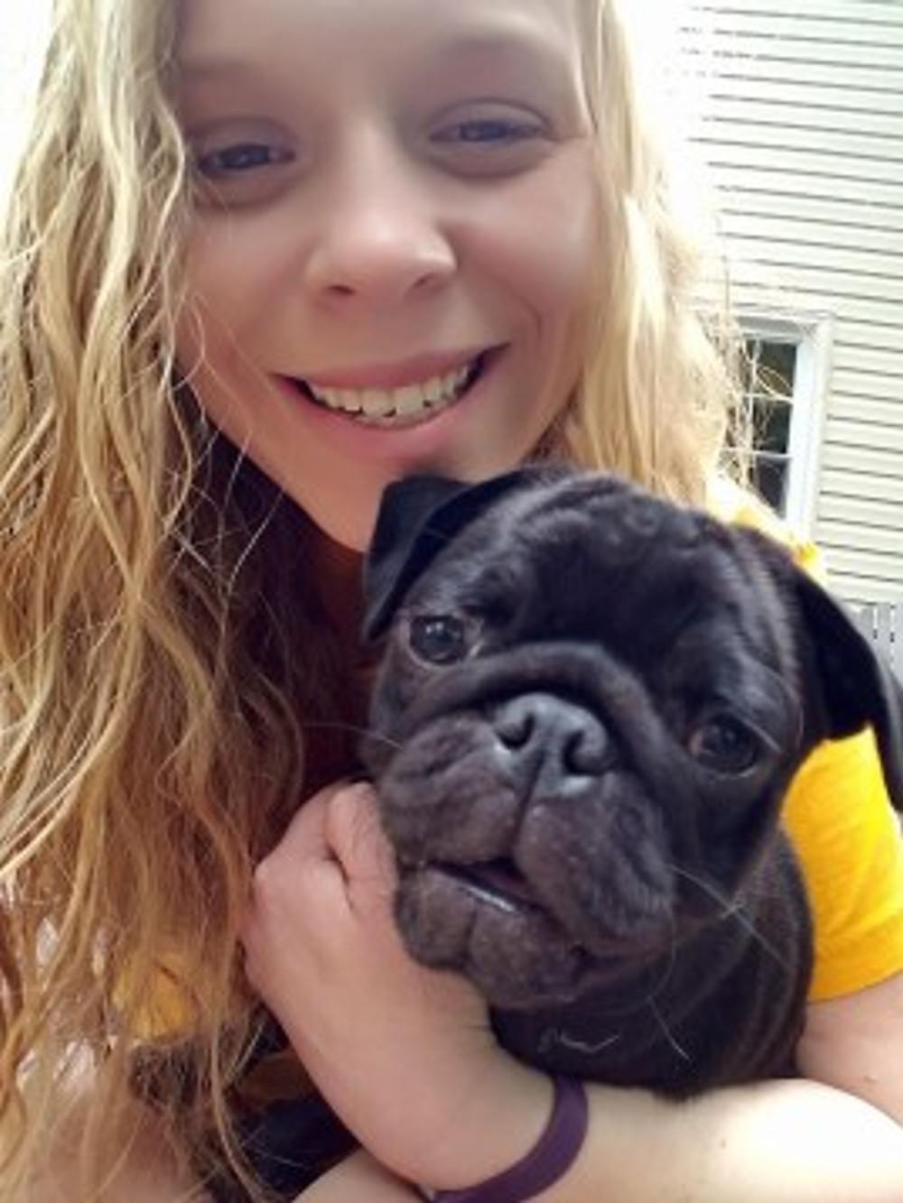 Selfie of Katie Mason with her black pug