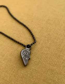 "Half of a friendship charm on a chain. Left side of a heart reads, ""Be- Frie-"""