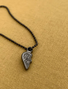 """Half of a friendship charm on a chain. Left side of a heart reads, """"Be- Frie-"""""""