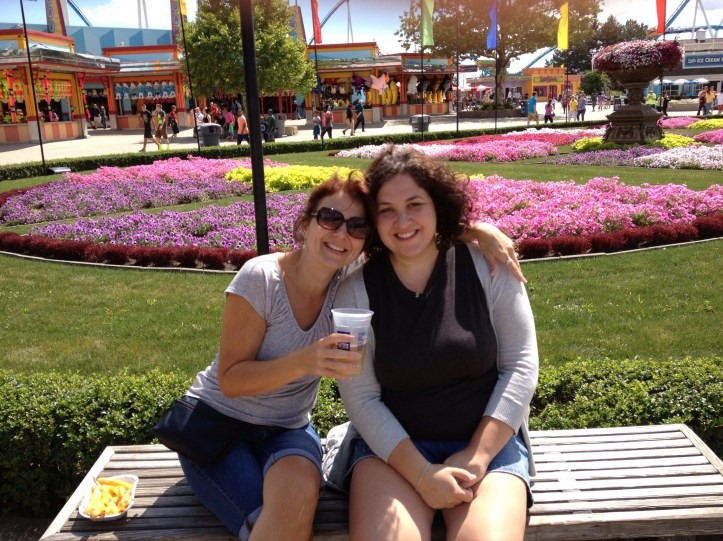 Mother and daughter lean against eachother on bench at Cedar Point amusement park.