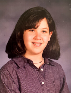 Headshot of 12-year-old white girl with dark shoulder-length hair and braces.