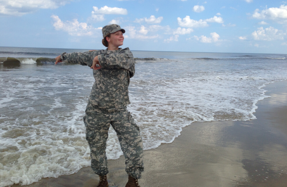 Young woman dances hula in military uniform along beach with the ocean behind her
