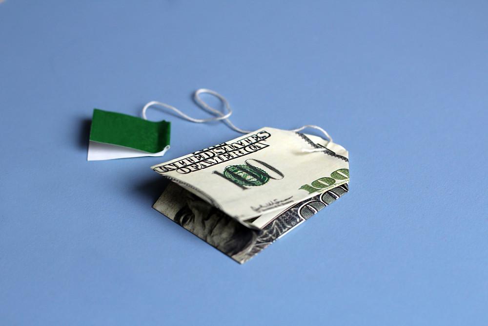 A 100 dollar bill folded to resemble a tea bag