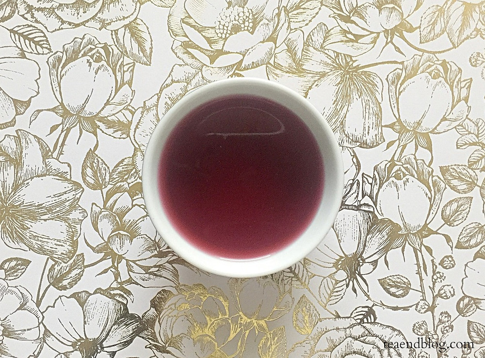 An aerial view of steeped hibiscus tea in a round white tea cup