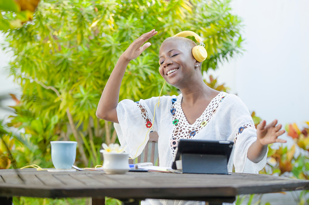 Young beautiful smiling African American woman sipping tea with headphones