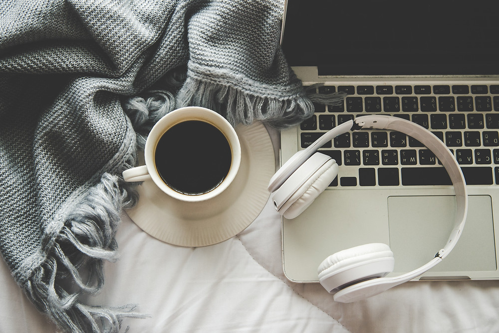 Tea with sweater-like blanket and headphones sitting atop a laptop with tea filled tea cup