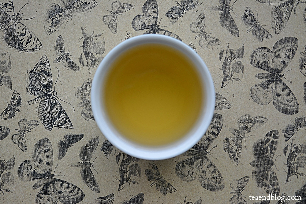 Aerial view of Dandelion Root Tea by Buddha's Herbs Blended in a white cup with a black and cream colored butterfly background