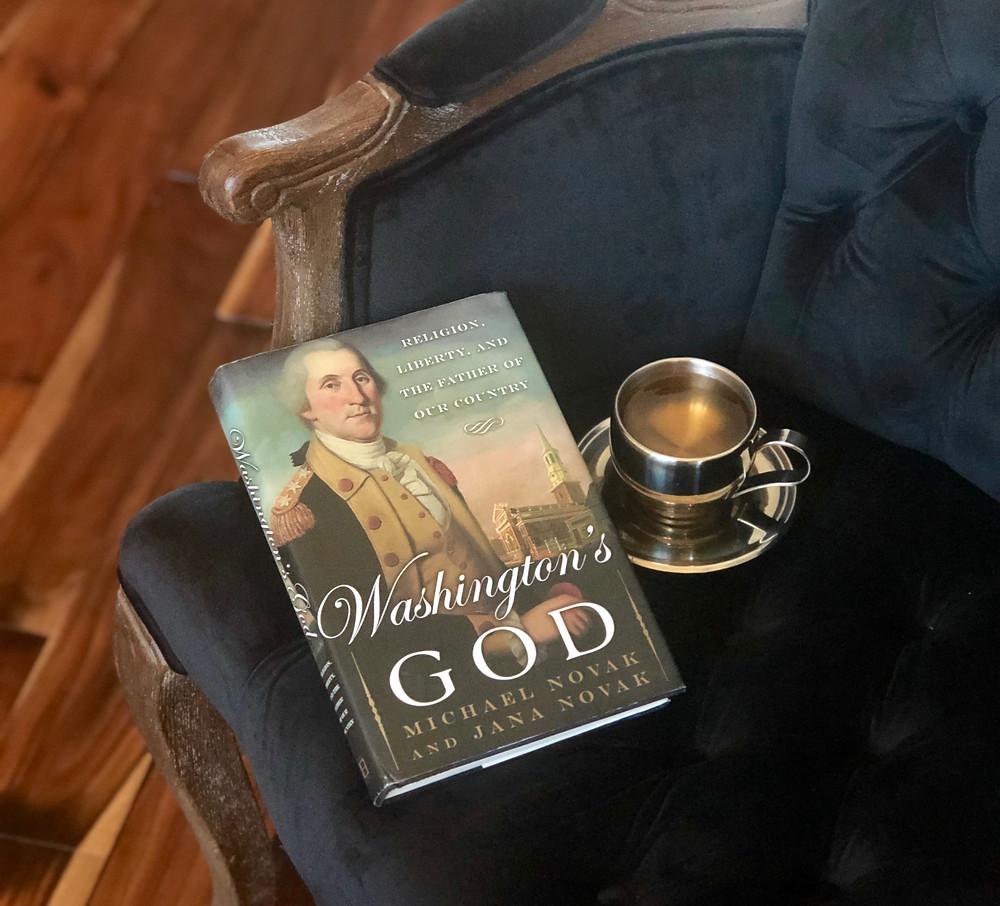 """Washington's God"" by Michael Novak & Jana Novak sitting on a black velvet chair with a silver tea cup and saucer"