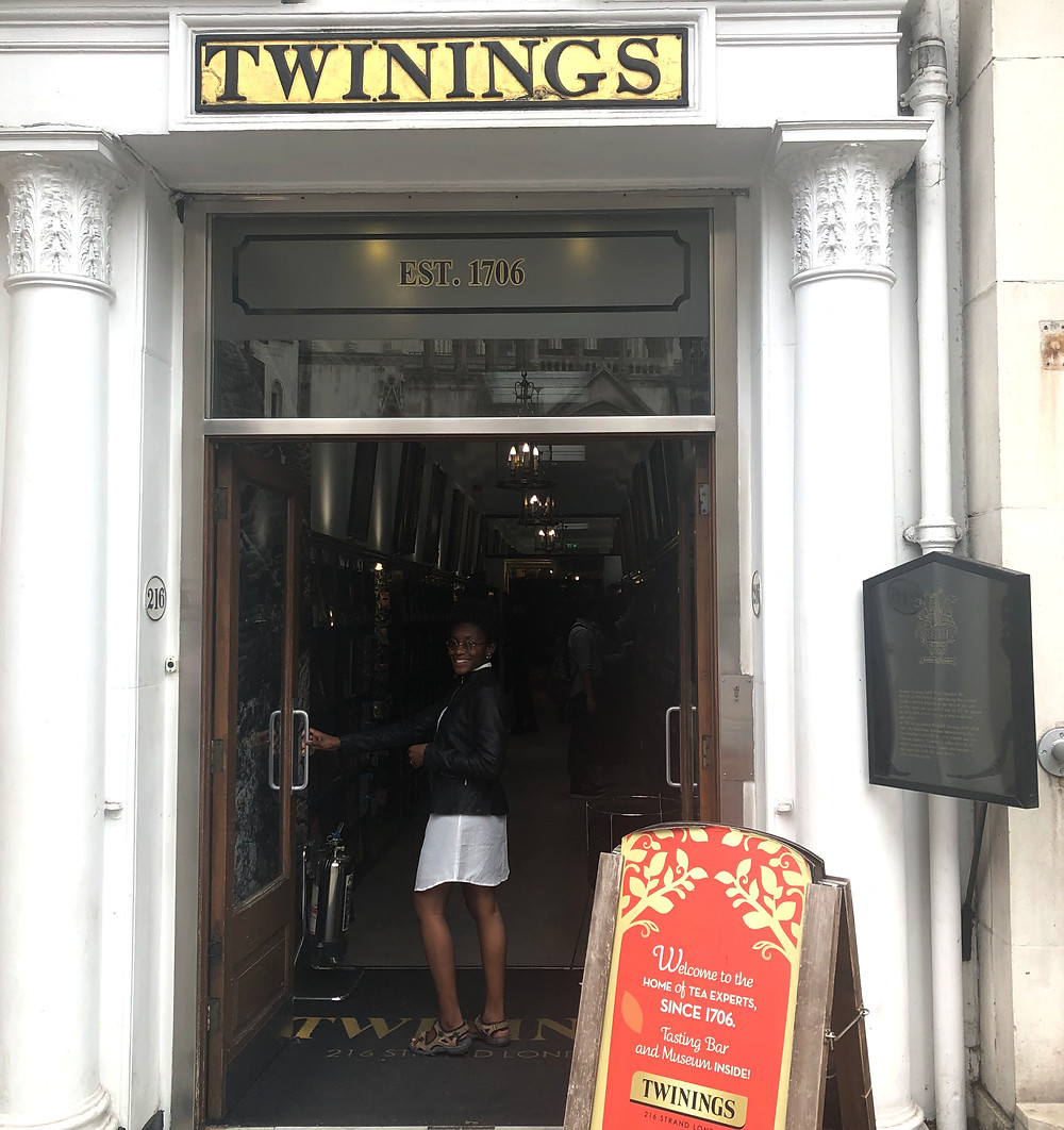 Gabie standing holding the handle to the door at the entrance of the Twinings Tea Shop