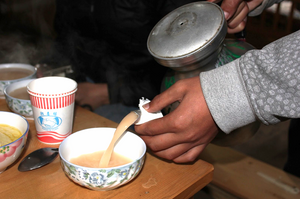 Tibetan pouring the national beverage, Dri-butter Tea.