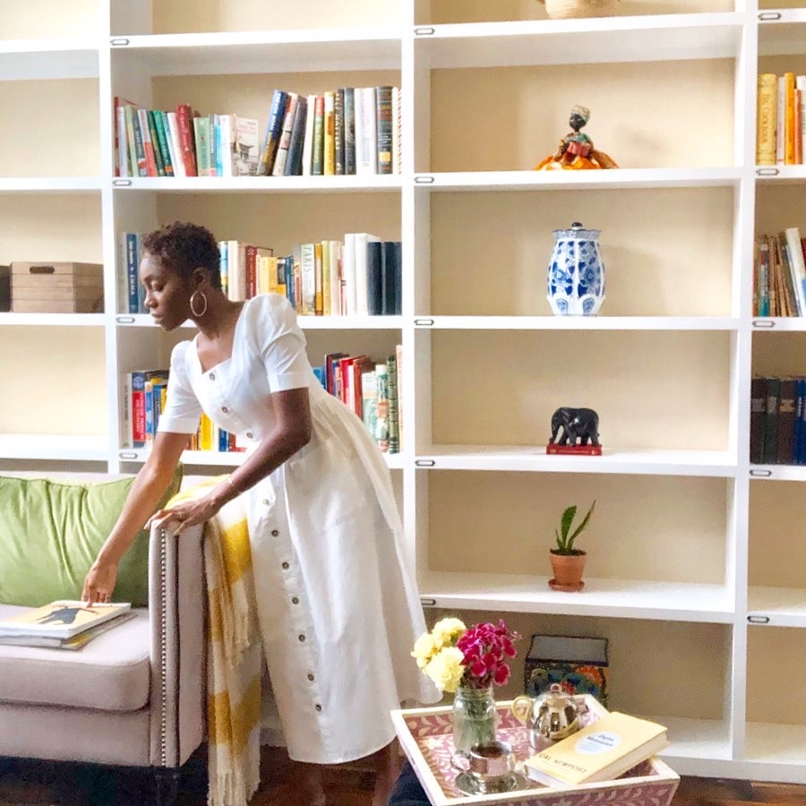 Gabie from Tea End Blog reaching  for magazines while standing in front of her home library