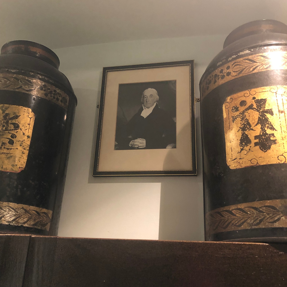 Photograph of a gentleman from the Twinings household hung between two large vintage tea tins