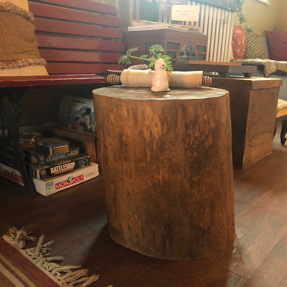 A red bench and a coffee table made from a tree stump