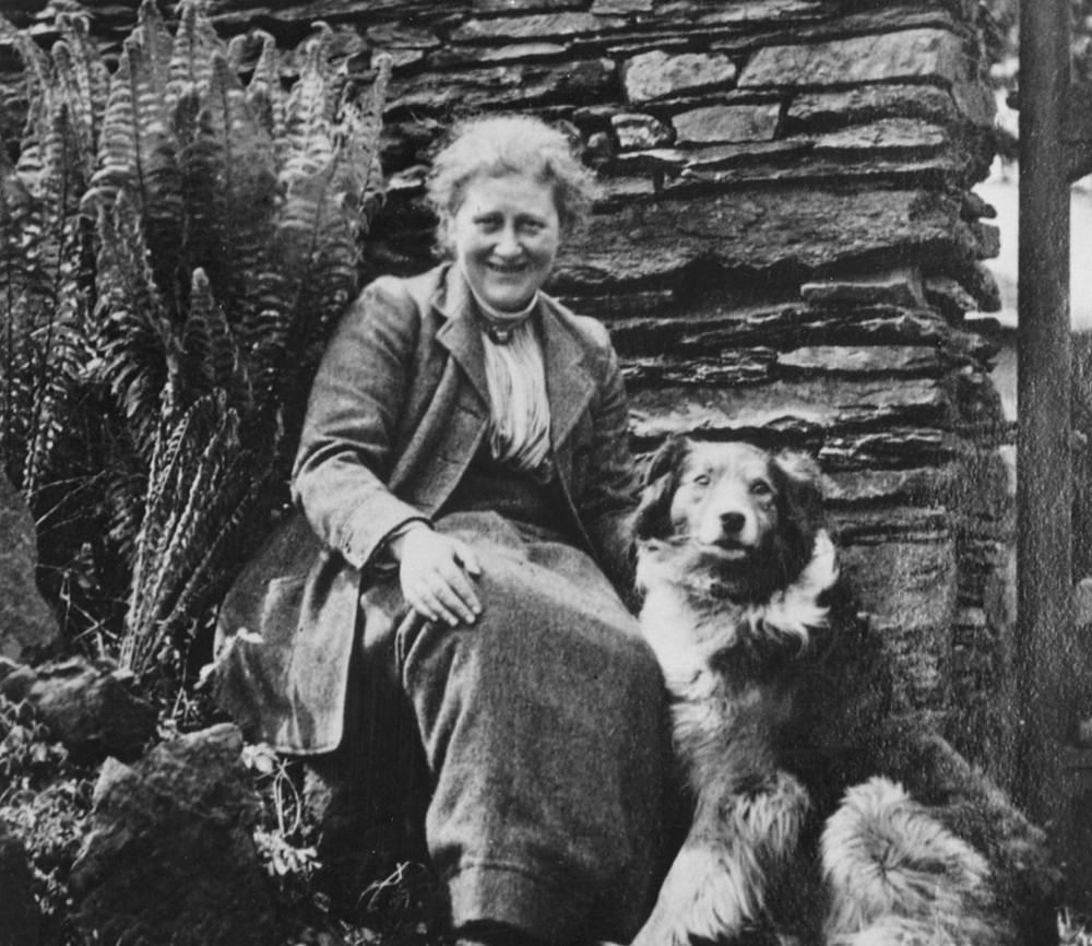 Beatrix Potter sitting outdoors with her dog