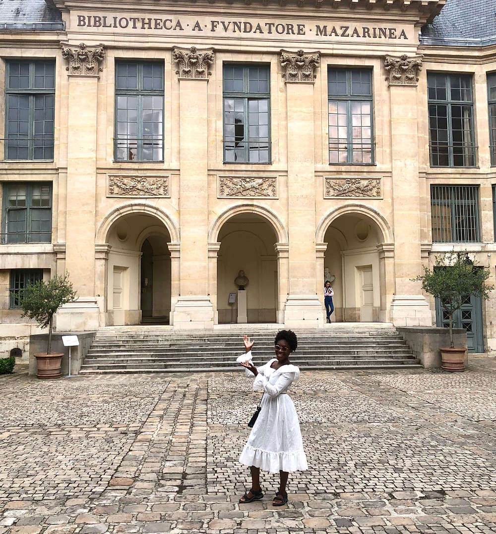 Gabie standing in front of the entrance to The Mazarin Public Library