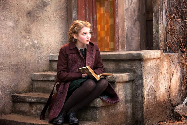 Liesel sitting on her doorsteps and gazing up with an open book in her hands in The Book Thief