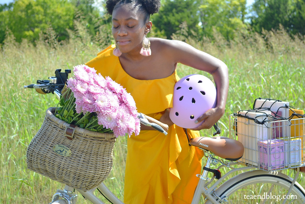 Gabie in a yellow dress leaning over her bike to smell the pink flowers in her bike basket while holding her pink bike helmet.