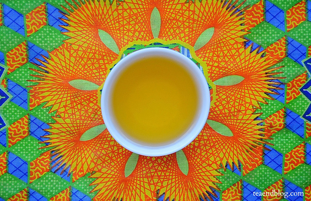 Aerial view of Ashwagandha Root & Jasmine Green Tea by Atman Tea Co. in a white cup with a yellow, blue, orange, and green background