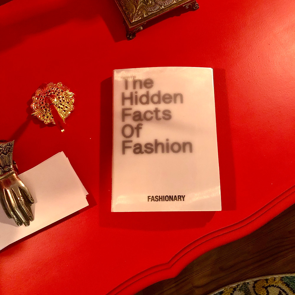 "Aerial photo of ""The Hidden Facts of Fashion"" by Fashionary on orange buffet"