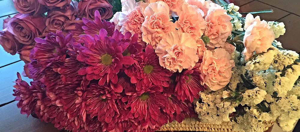 Flowers used: pink and purple roses; seasonal mini pink carnations; white statice; purple pom daisy