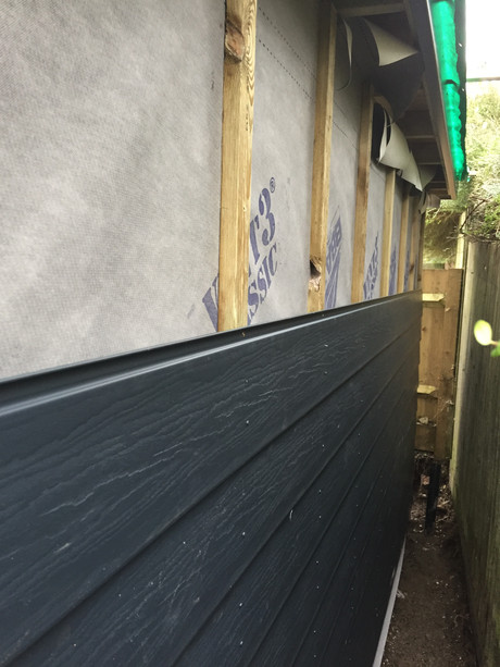 Cabin rear wall clad with wood effect composite to reduce cost